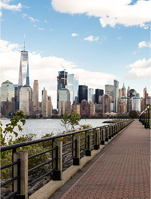Waterfront walkway in Jersey City with paved stone path, views of Hudson River and Manhattan behind.