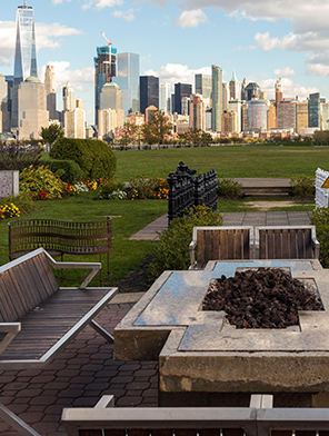 Professionally landscaped park with flowering plants and seats around a fire pit, NYC in background.