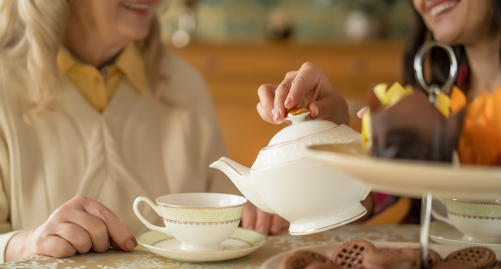 Hands of young woman with white china teapot pouring tea into cup of her senior mother